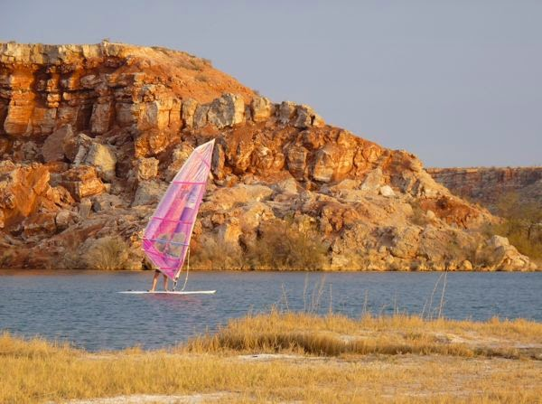 Sailboard on lake with cliff backdrop