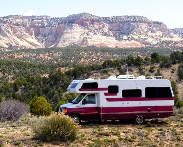 Motorhome in front of distant cliffs