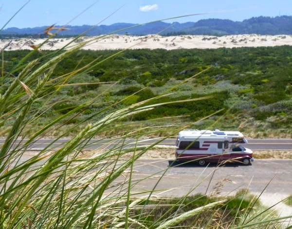 RV with sand dunes behind