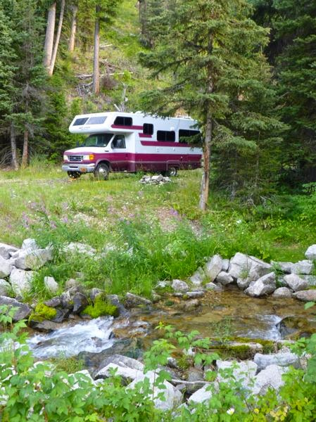 Motorhome in forest by stream