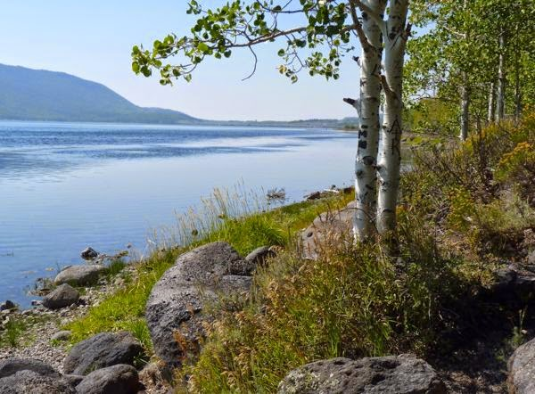 Lake with rocky shore and distant mountain