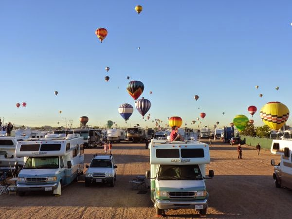 Lots of balloons floating over top of rigs