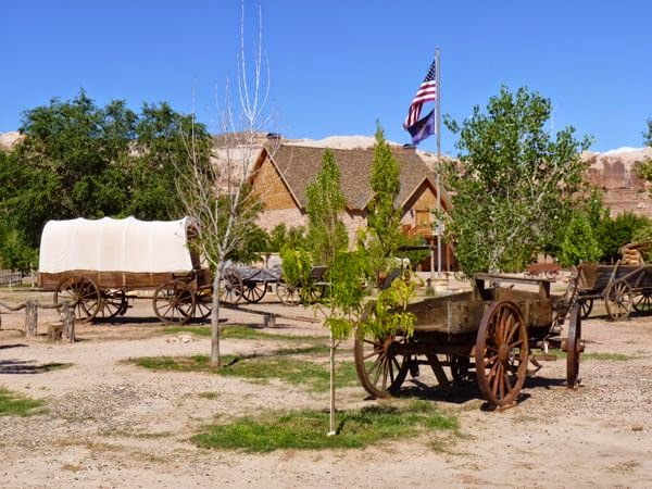 Cover wagon, flag pole and stone building
