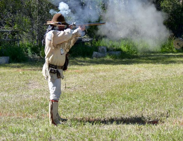 Man, rifle, smoke from shooting