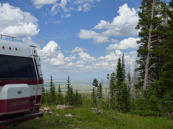RV, trees, valley, clouds