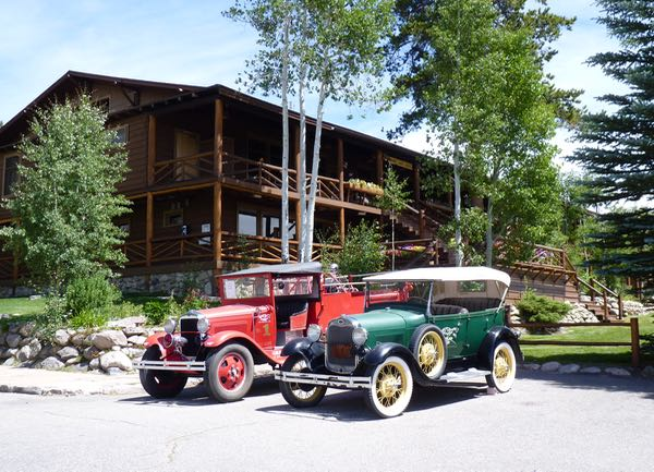 Building, old cars, trees